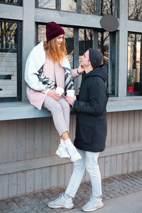 Sinnliche stilvolle Paare in trinkendem Kaffee der Liebe auf dem Straßencafé im kalten Winterwetter, den Spaß habend zusammen im  stockbilder