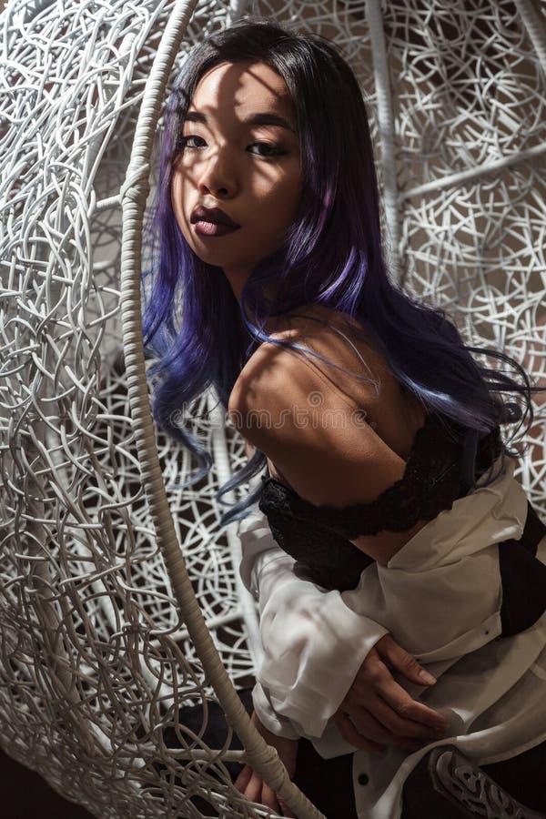 Sinnliche verlockende Frau mit dem farbigen Haar, das im Rattan Chai sitzt stockfoto