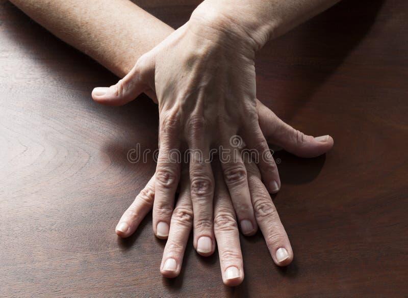 Sinnliche weibliche Hände, die sich zusammen für Verwirrung berühren stockbild