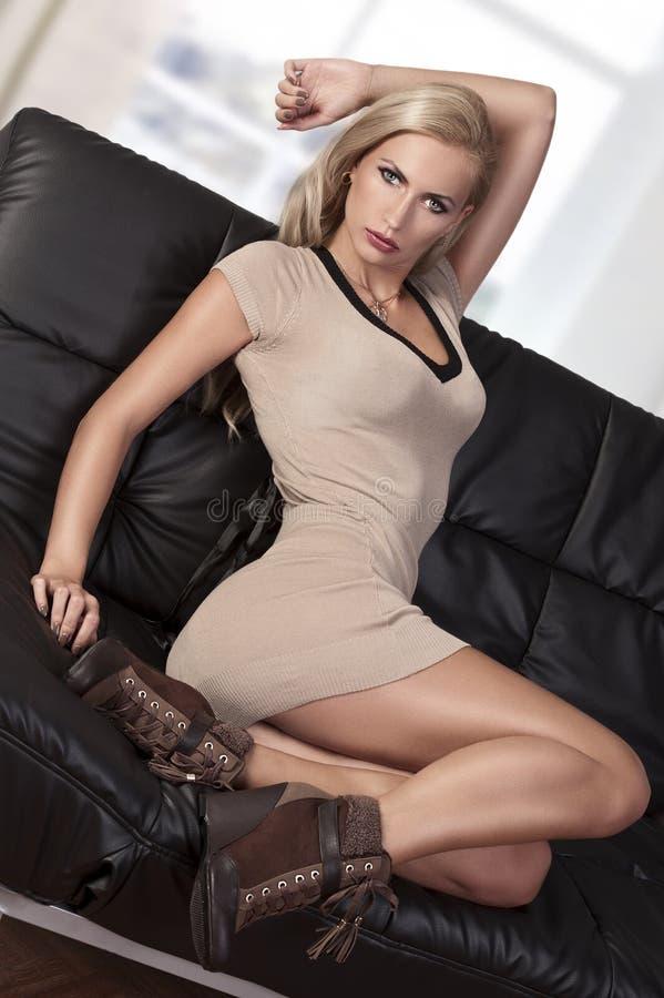Sinnliches Mädchen auf schwarzem Sofa stockbilder