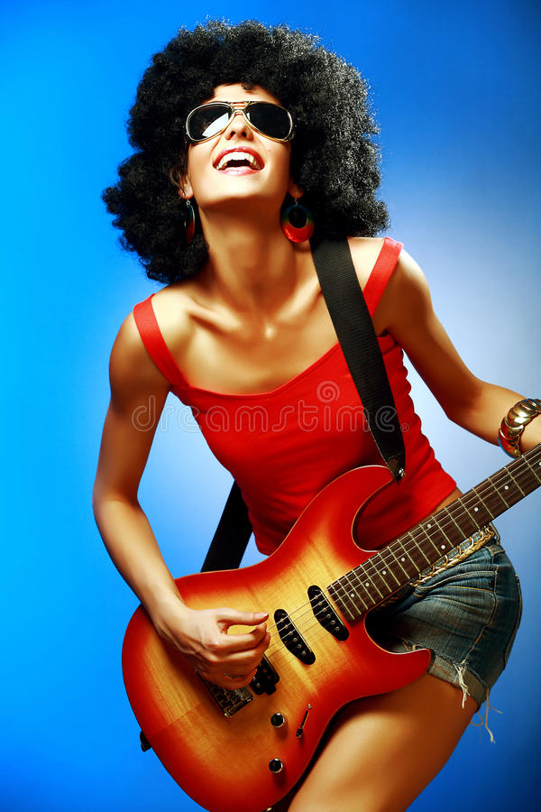 Sinnliches Mädchen, das auf der E-Gitarre spielt lizenzfreies stockfoto