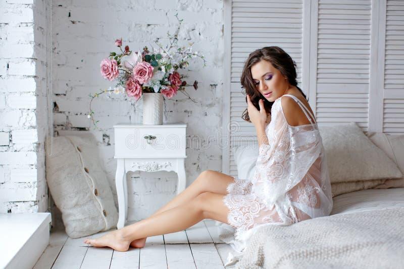 Sinnliches schönes und reizend schwangeres Brunettemädchen, das an sitzt stockfotos