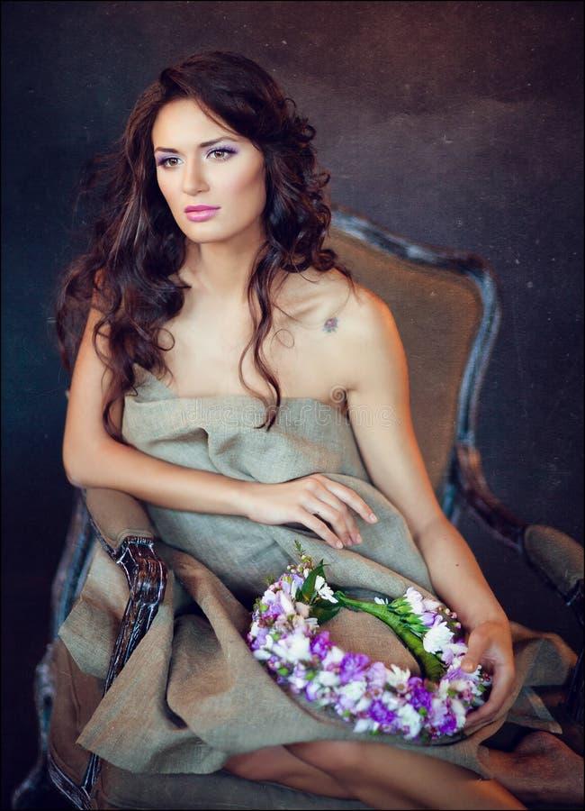 Sinnliches sexy schönes gelocktes Mädchen, das in einem Stuhl auf einem dunklen b sitzt stockbilder