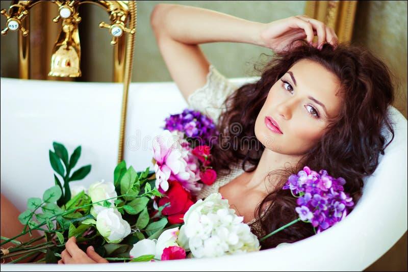 Sinnliches sexy schönes gelocktes Mädchen, das im Bad mit Blumen liegt lizenzfreie stockfotografie