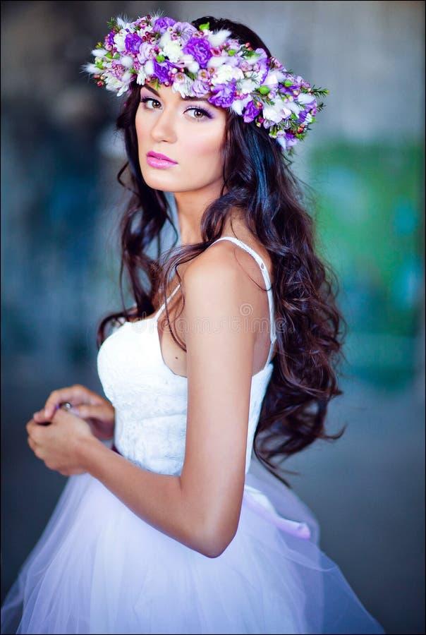 Sinnliches sexy schönes gelocktes Mädchen in einem weißen Kleid mit einem Blumen lizenzfreies stockbild