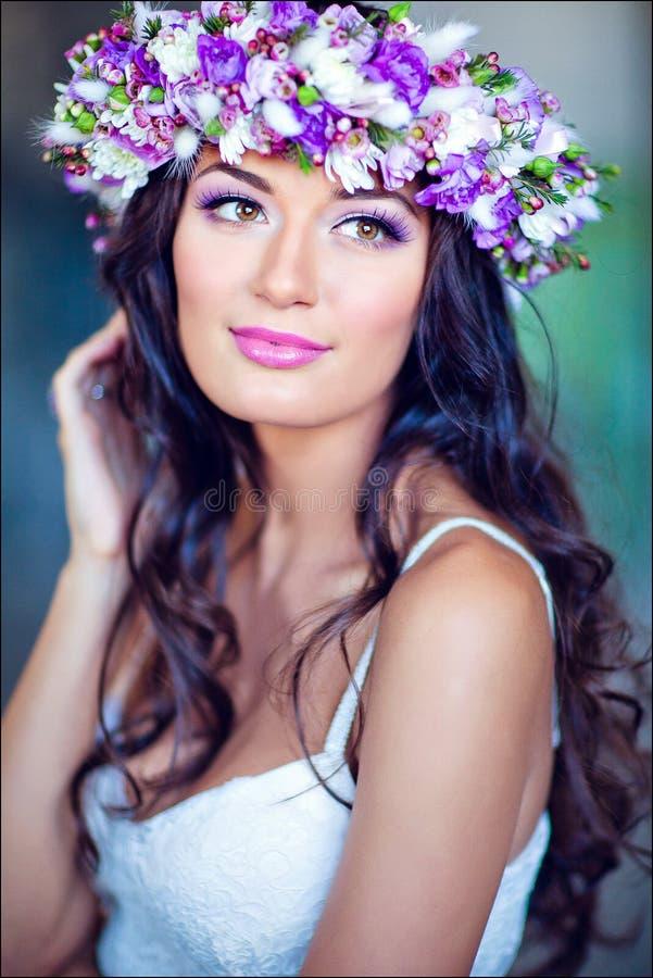 Sinnliches sexy schönes gelocktes Mädchen in einem weißen Kleid mit einem Blumen stockfotos