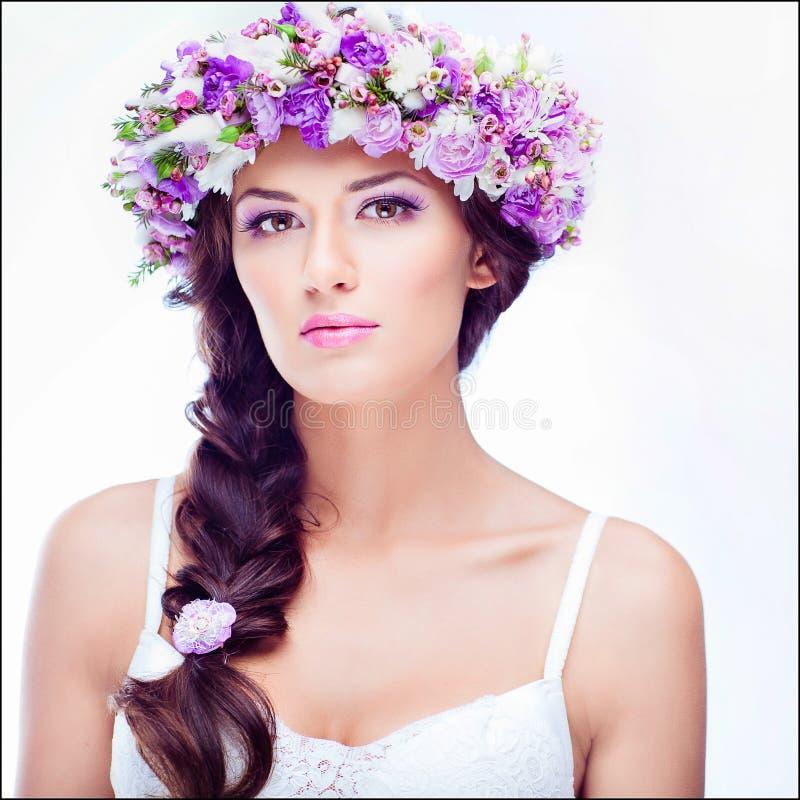 Sinnliches sexy schönes gelocktes Mädchen mit einem Blumenkranz auf ihr er stockfoto