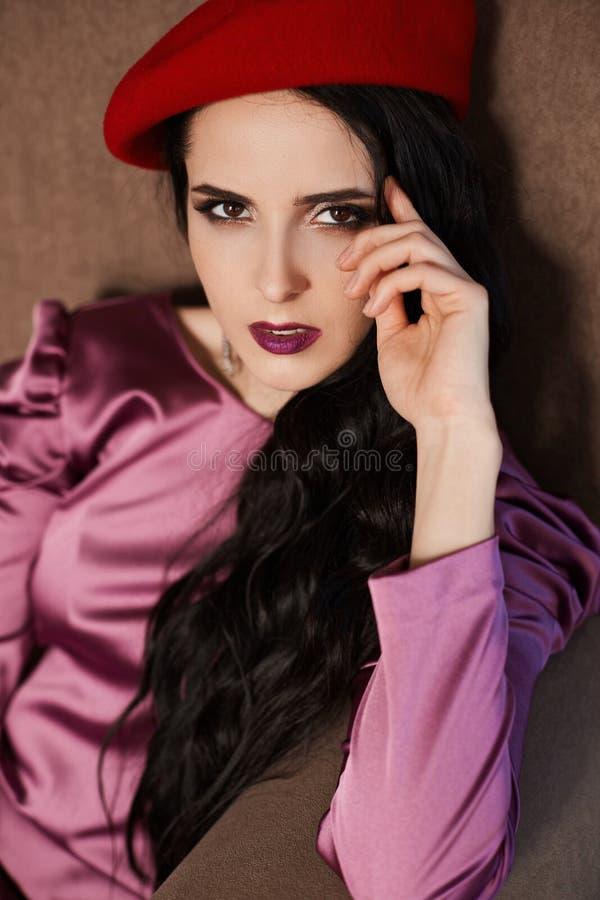 Sinnliches und schönes brunette vorbildliches Mädchen mit hellem Make-up im modernen roten Barett und in einem stilvollen rosa Kl stockfoto