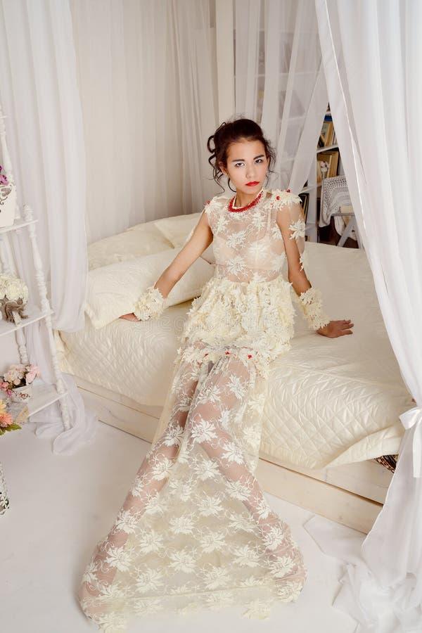 Sinnlig asiatisk flicka, i härligt damunderklädersammanträde på vit säng och att se upp på kameran arkivbilder