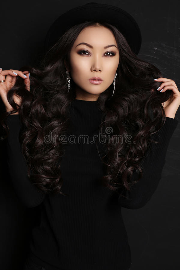 Sinnlig asiatisk kvinna med långt mörkt hår i svart klänning fotografering för bildbyråer
