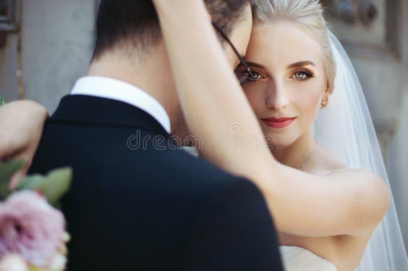 Sinnlig blond brud som kramar den starka brudgummen, framsidacloseup royaltyfria foton