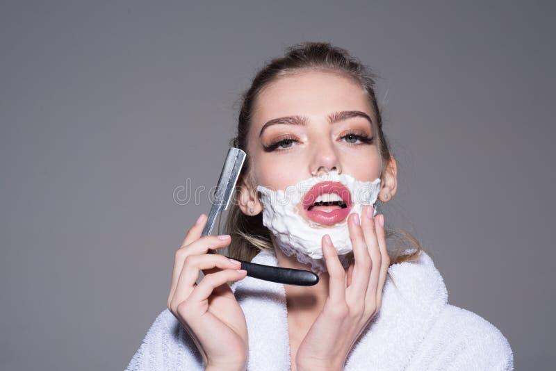 Sinnlig blond flicka i hållande snitt-hals för vit badrock rakkniv i hennes händer som isoleras på grå bakgrund härlig kvinna royaltyfri foto