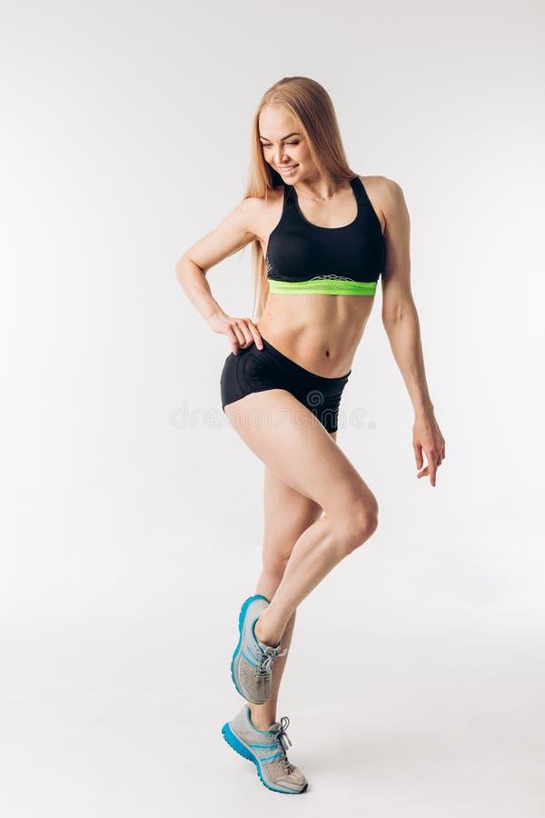 Sinnlig blond idrottskvinna med den perfekta kroppen som isoleras över vit bakgrund royaltyfria bilder