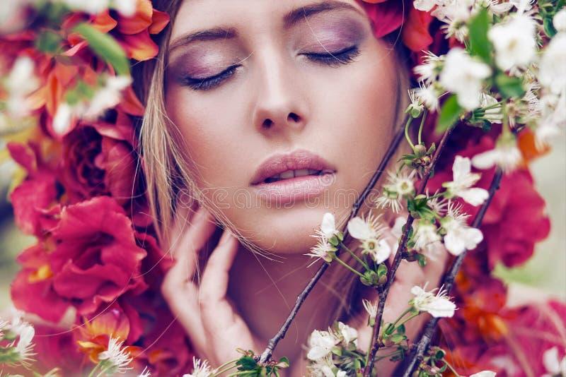 Sinnlig blond kvinna med blommor royaltyfri fotografi