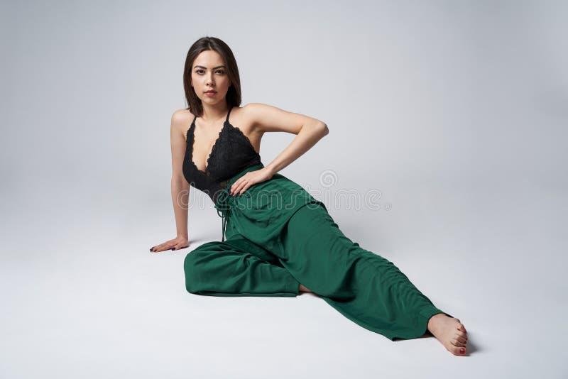 Sinnlig brunett som är kvinnlig i grön byxa och överkant med djup dekolletage arkivfoto