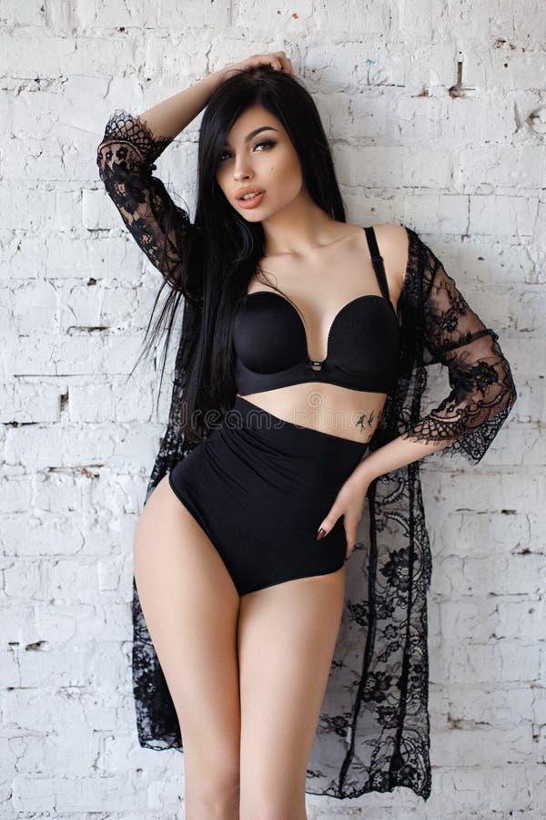 Sinnlig brunettkvinna med långt hår som poserar i sexig svart damunderkläder arkivbilder