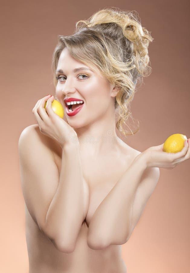 Sinnlig Caucasian blond flicka som poserar med två citroner i händer Framställning av en tugga arkivbild