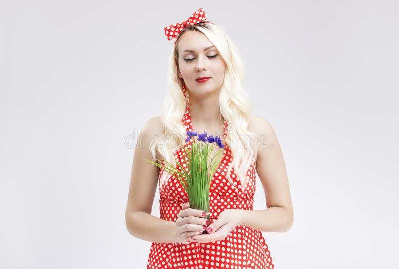 Sinnlig Caucasian blond kvinnlig i den röd polka prack klänningen Dreamin royaltyfria foton