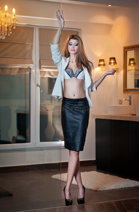 Sinnlig dräkt för elegant kvinna som i regeringsställning poserar mode. Härlig och sexig blond ung kvinna som bär den sexiga behån arkivfoto