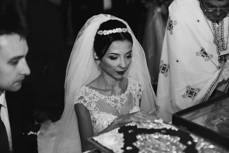 Sinnlig emotionell brud och brudgum som tar löften på bibeln i ch arkivfoto