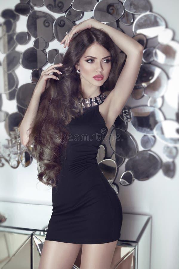 Sinnlig flickamodell för härlig brunett i kort svart klänningposin royaltyfri bild