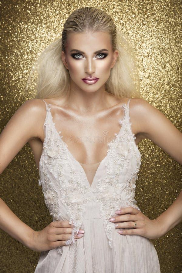 Sinnlig härlig blond kvinna som poserar i den vita klänningen över guld b arkivfoton