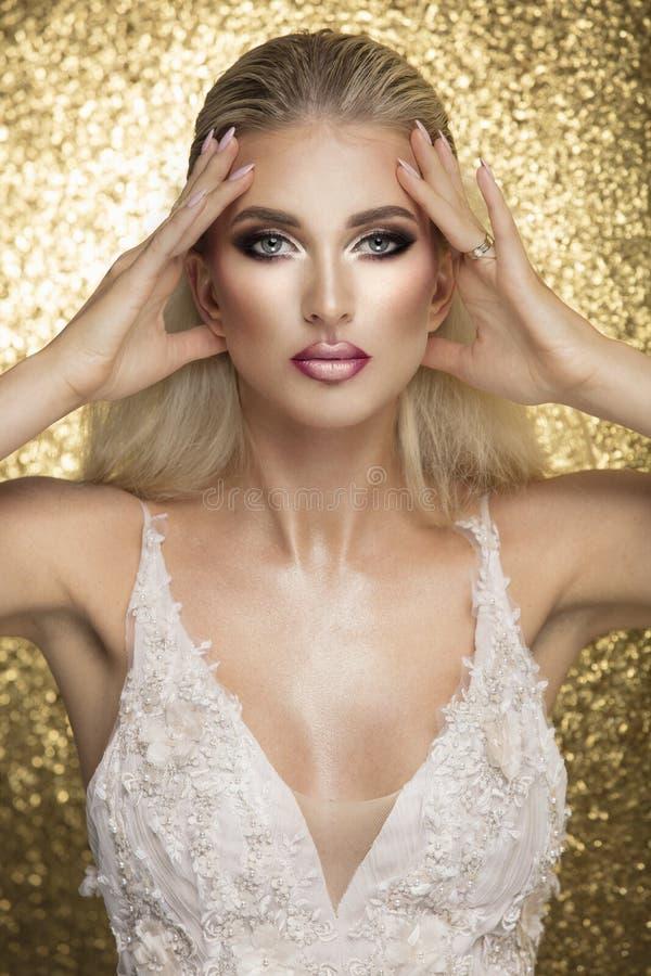 Sinnlig härlig blond kvinna som poserar i den vita klänningen över guld b arkivfoto
