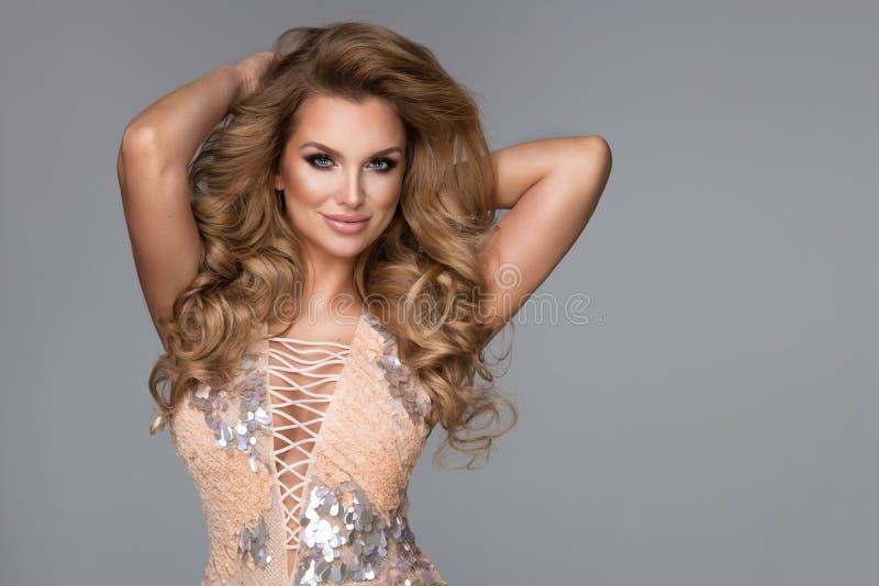 Sinnlig härlig blond kvinna som poserar i glänsande klänning fotografering för bildbyråer