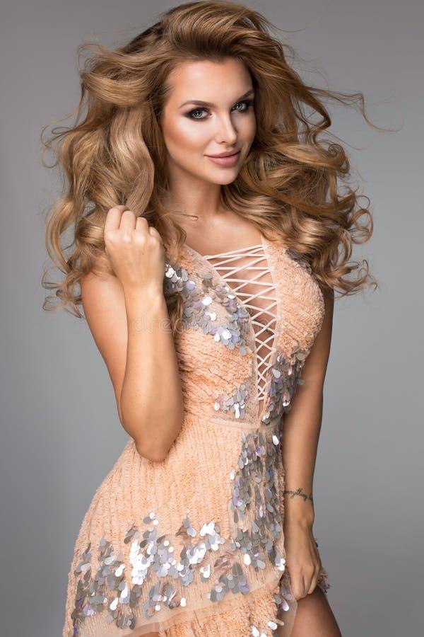 Sinnlig härlig blond kvinna som poserar i glänsande klänning arkivbild