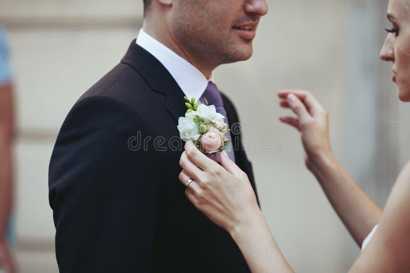 Sinnlig härlig brud som sätter på blommaboutonniere på handsom fotografering för bildbyråer