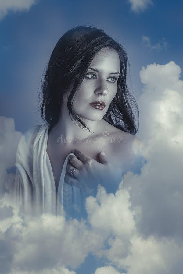 Sinnlig härlig kvinna i moln, mithologybegrepp brunett arkivbild