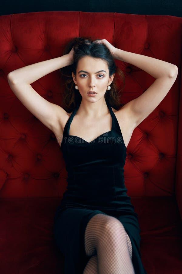 Sinnlig h?rlig kvinna som poserar i sexig svart kl?nning p? den r?da soffan arkivbilder
