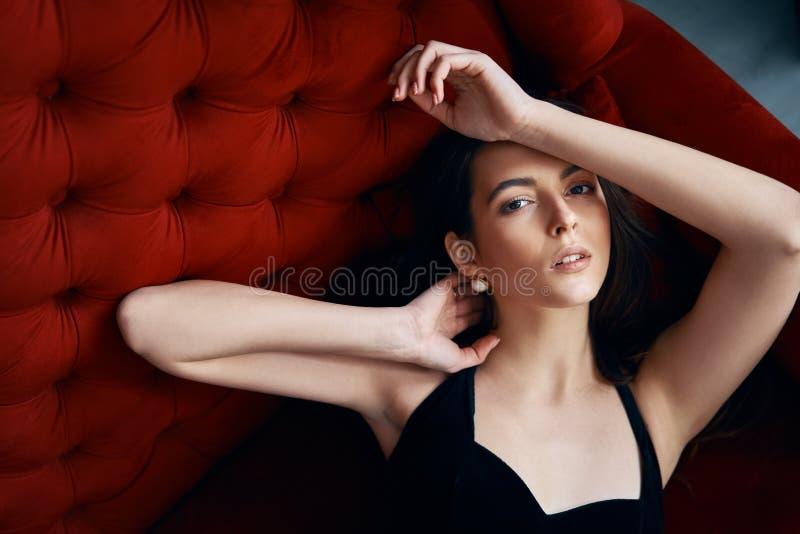 Sinnlig h?rlig kvinna som poserar i sexig svart kl?nning p? den r?da soffan royaltyfria foton
