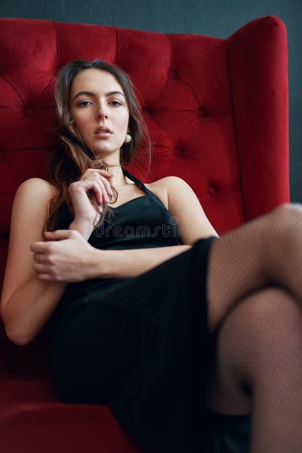 Sinnlig h?rlig kvinna som poserar i sexig svart kl?nning p? den r?da soffan royaltyfri foto