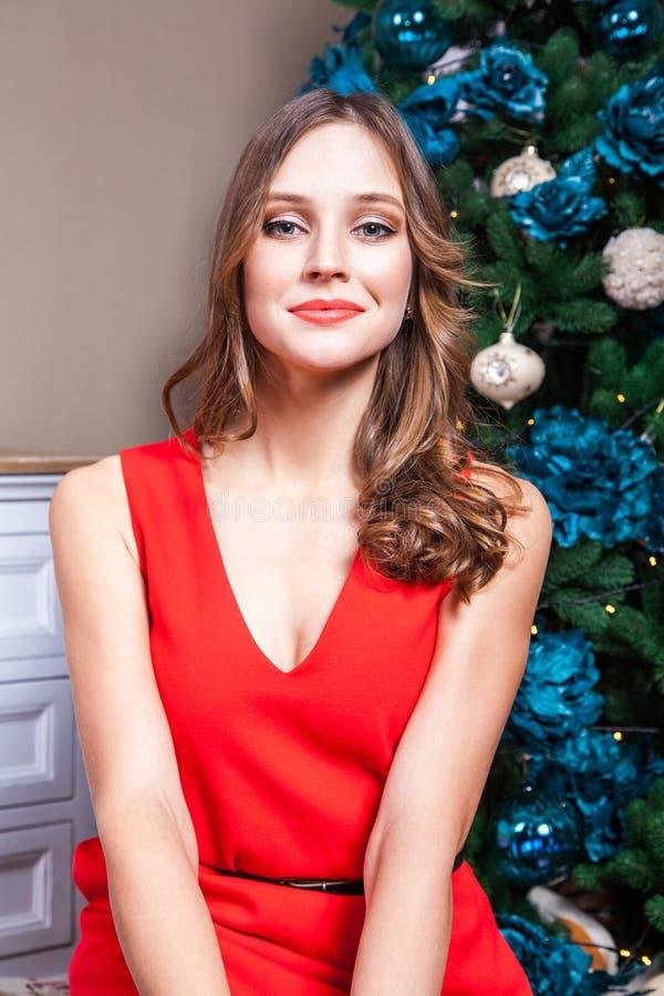 Sinnlig kvinna i en härlig röd klänning och makeup som ser kameran med passion arkivbilder