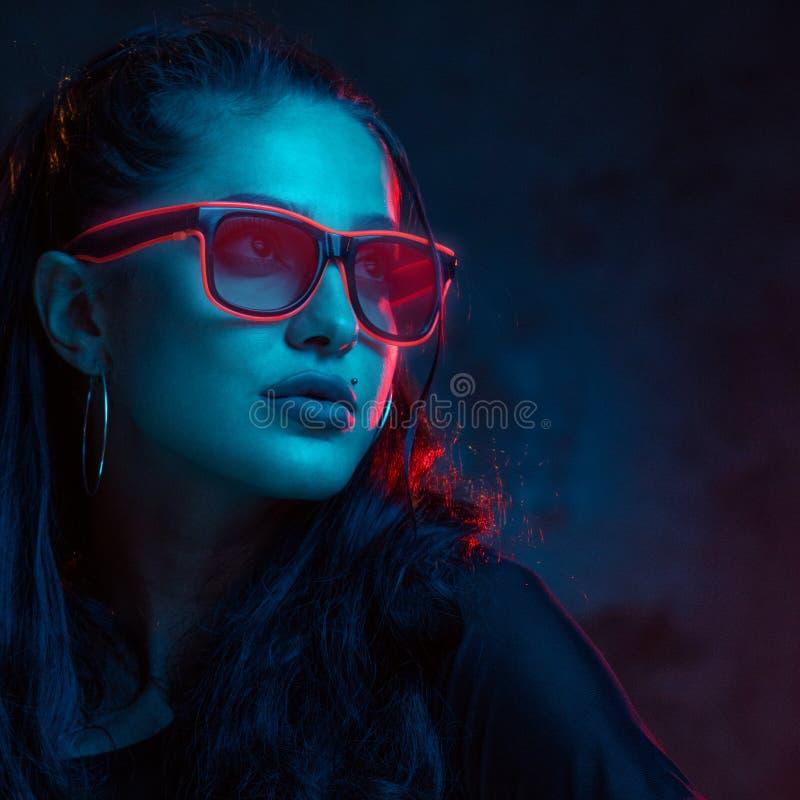Sinnlig kvinna i neonexponeringsglasstående royaltyfri bild
