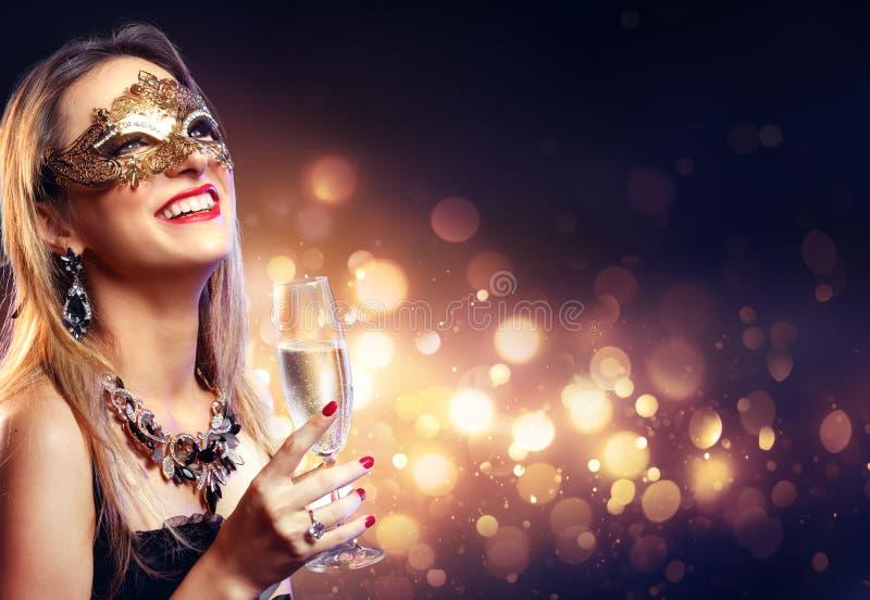 Sinnlig kvinna med den guld- maskeringen och Champagne royaltyfri foto