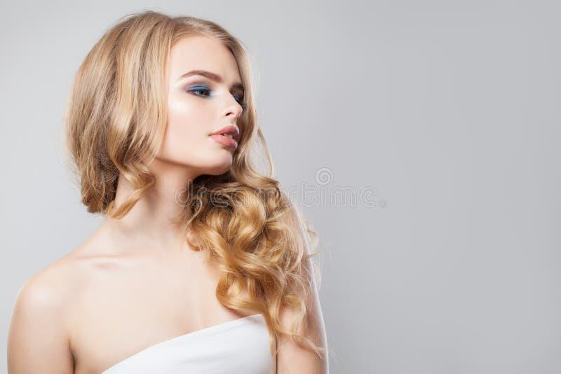 Sinnlig kvinna med långt skinande hår och makeup på vit bakgrund royaltyfri foto