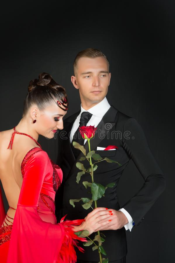 Sinnlig kvinna och man med rosblomman Kvinna i röd klänning och macho i smoking Par av förälskade balsaldansare red steg royaltyfri bild