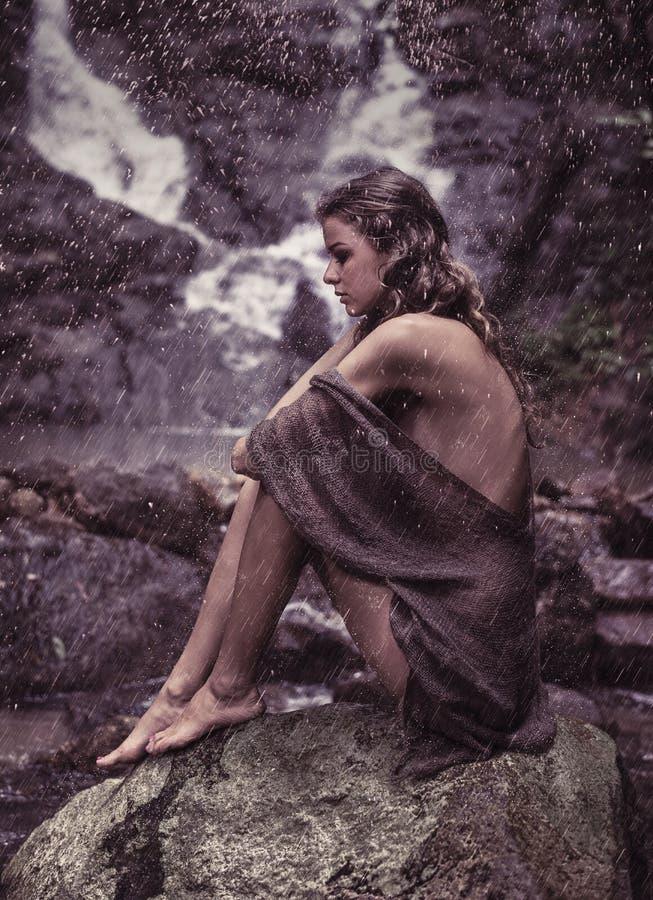Sinnlig kvinna som nära vilar till vattenfallet royaltyfri fotografi