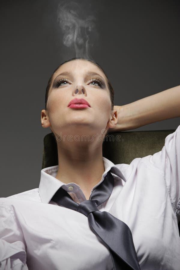 Sinnlig kvinna som röker en cigarett arkivfoton