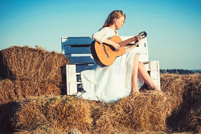 Sinnlig kvinnalekgitarr på träbänk Kvinnagitarristen utför musikkonsert Akustisk gitarr för albinoflickahåll royaltyfri foto