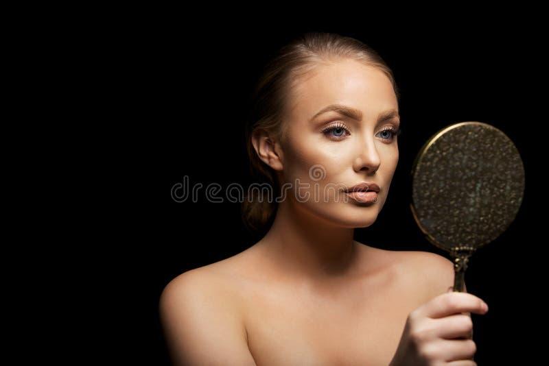Sinnlig kvinnlig modell som ser i sminkspegel arkivbild