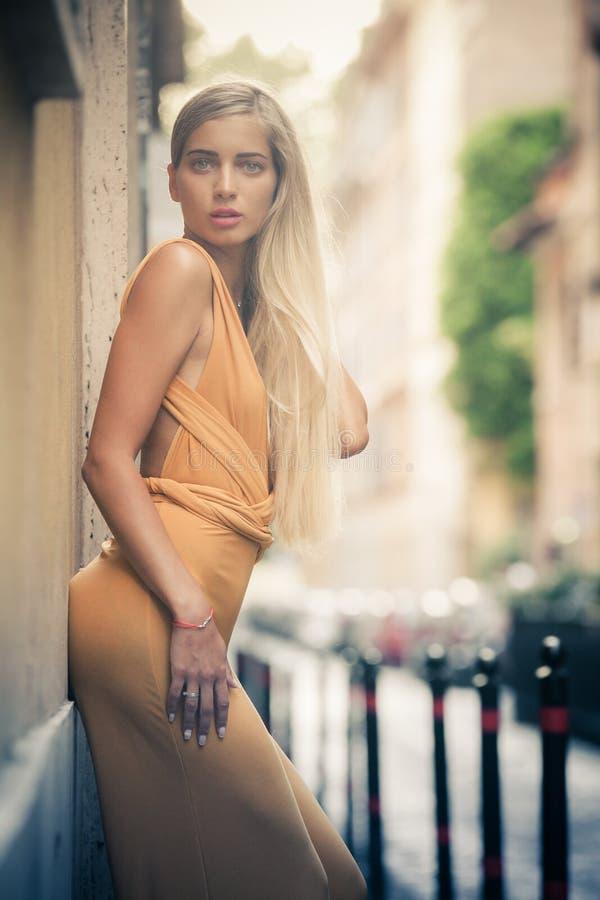 Sinnlig och attraktiv ung blond kvinna som lutar mot väggen på gatan i staden arkivfoton