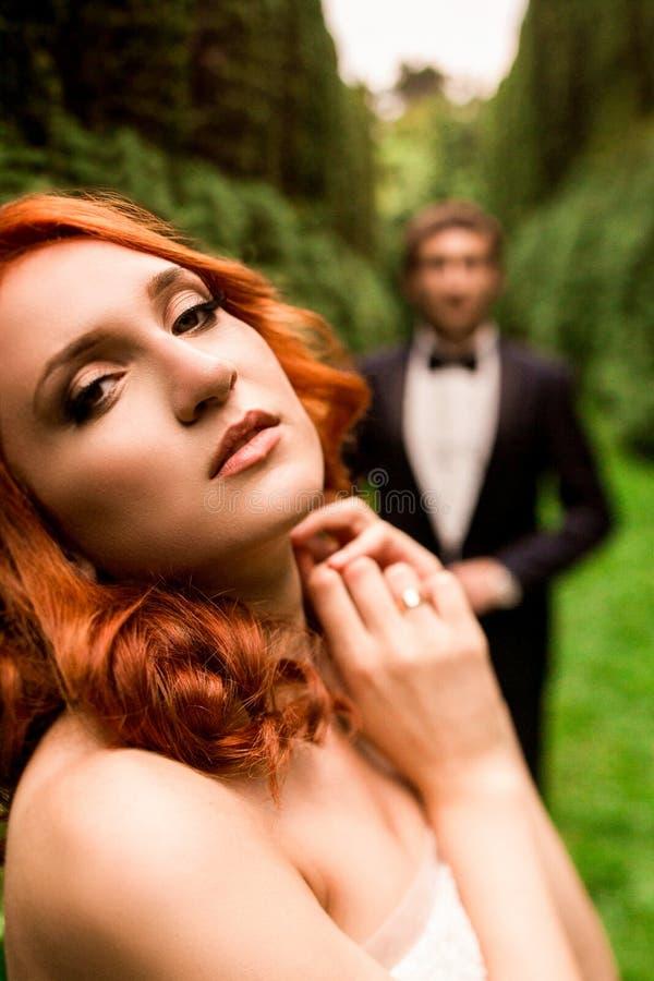 Sinnlig rödhårig manbrud och brudgum bak henne arkivfoton