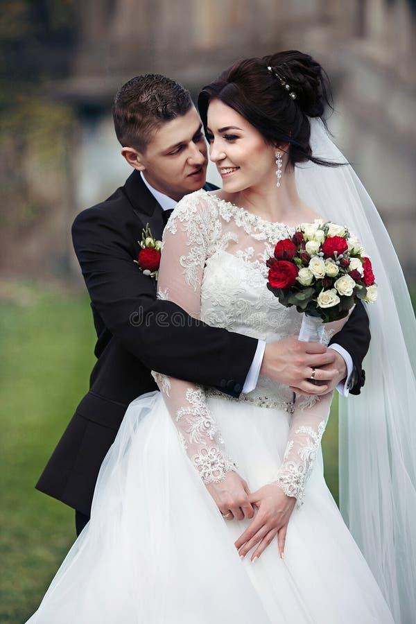 Sinnlig romantisk brudgum som bakifrån kramar den härliga bruden med arkivbild