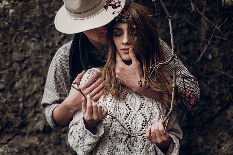 Sinnlig romantisk man i cowboyhatt som kramar en härlig zigensk bru fotografering för bildbyråer