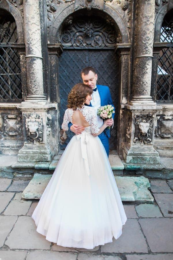 Sinnlig romantisk nygift personbrud och brudgum som framme kramar av gammal bulding med kolonner fotografering för bildbyråer