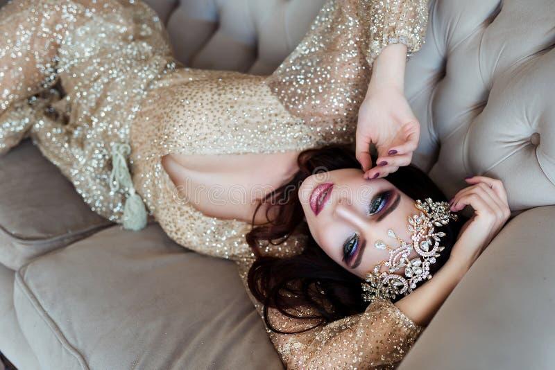 sinnlig skönhet Härlig ung kvinna med stilfullt brunetthår och den eleganta klänningen som vilar i lyxigt vitt klassiskt rum royaltyfri bild
