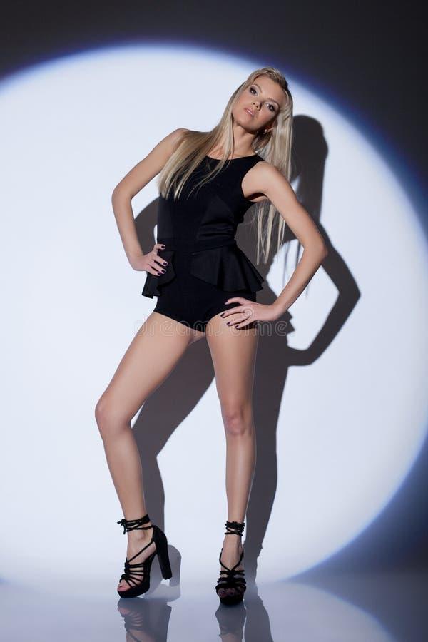 Sinnlig slank dansare som poserar i strålkastare royaltyfria bilder